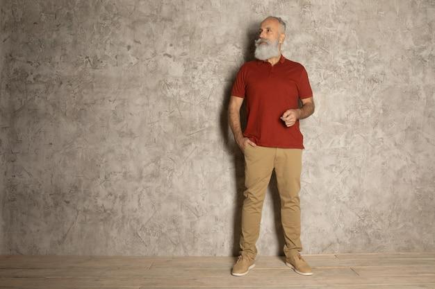 Barba perfetta primo piano dell'uomo barbuto senior che sta contro il fondo grigio