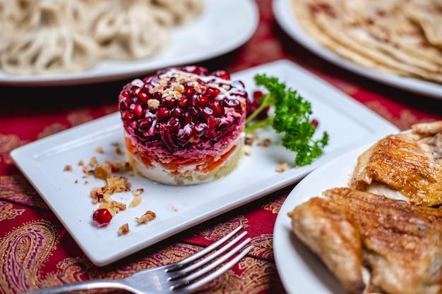 Barbabietola dell'insalata del melograno di vista laterale con il mayp della carota della patata e la noce su un piatto