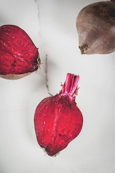 Barbabietole crude fresche dell'agricoltore biologico con foglie, intere e in sezione, su un tavolo da cucina in marmo bianco.