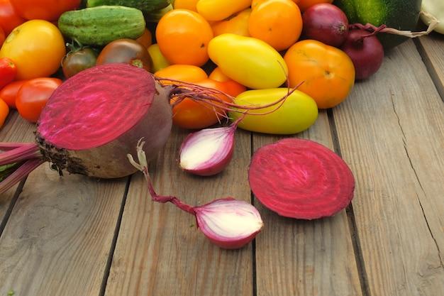 Barbabietole e cipolle a fette si trovano su una tavola di legno su uno sfondo di diverse verdure luminose. raccolto e concetto di cucina.