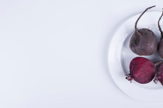 Barbabietole intere e metà in un piatto bianco sul lato destro.