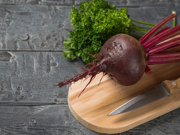 Barbabietole rosse fresche con un coltello e un mazzo di prezzemolo sul tagliere.