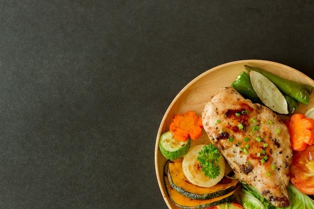 Barbecue al petto di pollo fatto in casa o bistecca su piatto di legno servito con verdure grigliate.