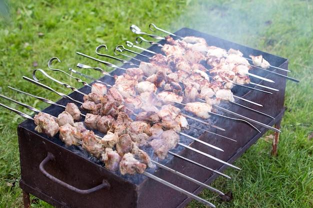 Barbecue all'aperto in una luminosa giornata estiva. close-up di pezzi di carne shish kebab su spiedini di torrefazione.