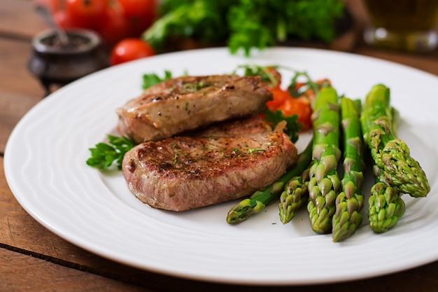 Barbecue bistecca di manzo alla griglia con asparagi e pomodori.