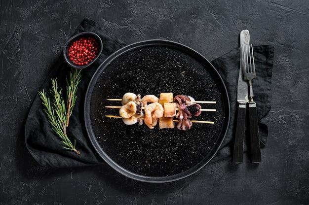 Barbecue con frutti di mare kebab su spiedini di legno con gamberi, polpi, calamari e cozze. vista dall'alto. spazio per il testo