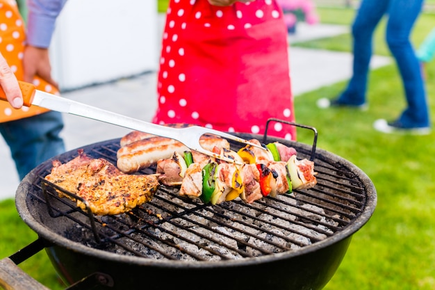 Barbecue della famiglia insieme nella casa del giardino