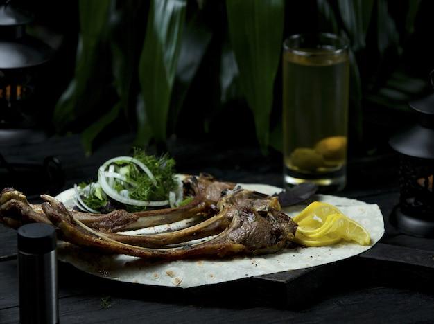 Barbecue di agnello servito in lavaash con erbe fresche e fettine di limone