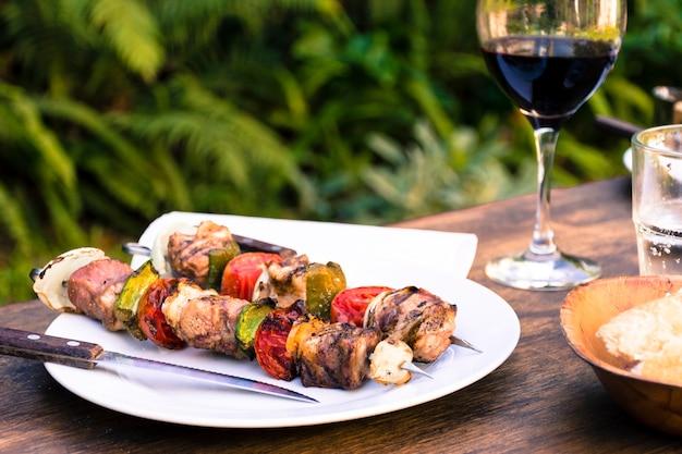 Barbecue di carne e verdure che serve a tavola e bicchiere di vino
