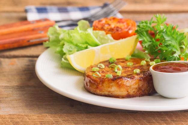 Barbecue di maiale o manzo fatto in casa o bistecca sul piatto bianco servito con verdure fresche.