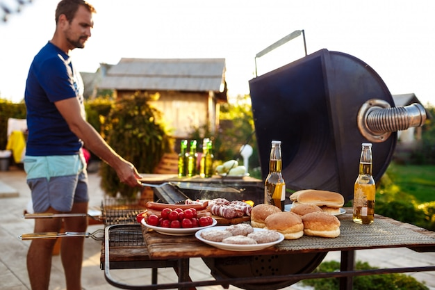 Barbecue di torrefazione del giovane sulla griglia nella campagna del cottage.