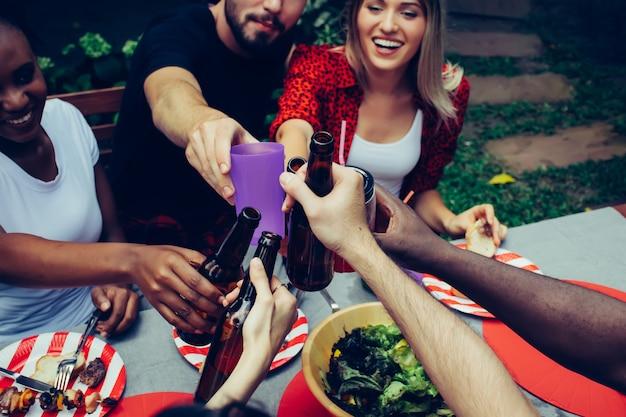 Barbecue e festa. felice di amici di gruppo con barbecue in natura