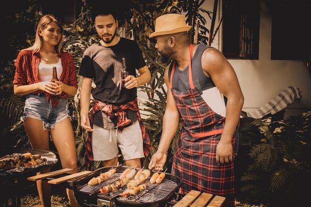 Barbecue e party. amici felici con barbecue party in natura