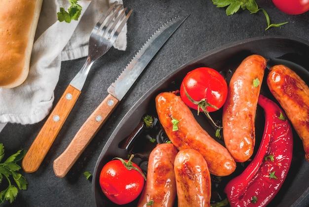 Barbecue. hot dog domestici. verdure grigliate. salsicce, pomodori e peperoni su una teglia grigliata, cotti. con spezie ed erbe. con pane ai panini. sul tavolo di pietra nera. copia spazio vista dall'alto