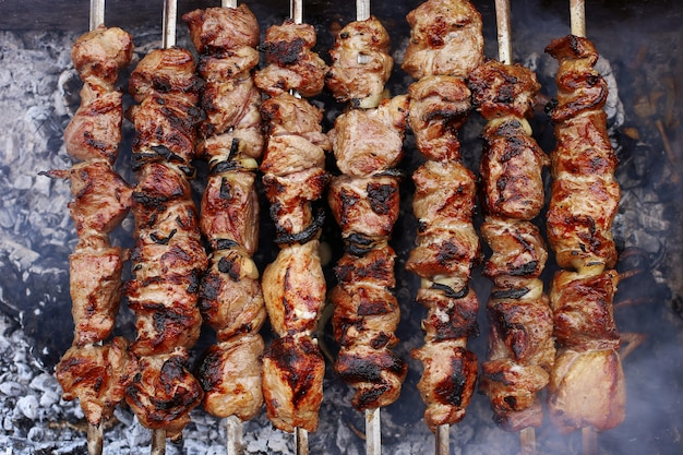 Barbecue in natura in estate. carne suina nel fumo sui carboni, alimento sano, primo piano, vista superiore.