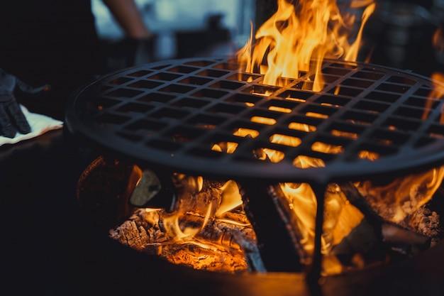 Barbecue, primo piano. cucinando professionalmente il cibo su un fuoco aperto su una griglia in ghisa.
