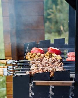 Barbecue shashlik kebab con alette e pomodori con pepe arrosto in chargrill allo spiedo