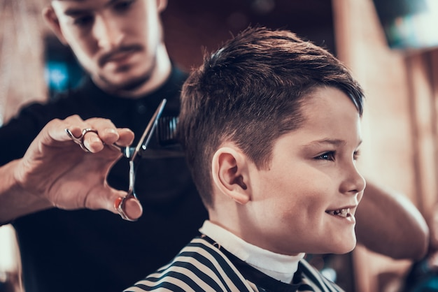 Barber clips handsome kid sides with scissors