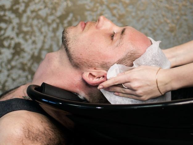 Barbiere. barbiere donna lavaggio testa di uomo, vista laterale