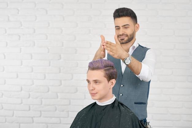 Barbiere che fa i capelli lilla che tonificano per il giovane cliente.