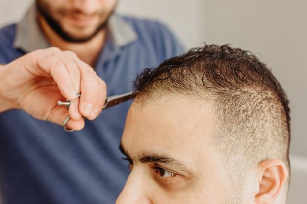 Barbiere che fa taglio di capelli alla moda con forbici professionali nel negozio di barbiere. taglio di capelli per uomo turco