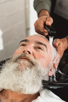 Barbiere che lava la testa al cliente anziano