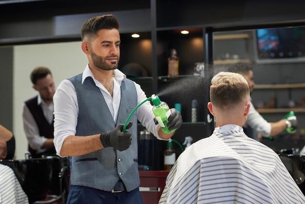 Barbiere che spruzza acqua sul taglio di capelli del cliente usando la bottiglia dello spruzzatore.