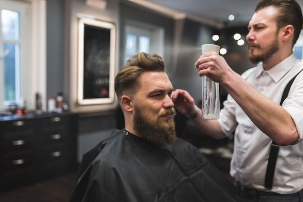 Barbiere che spruzza i capelli del cliente