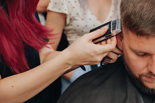 Barbiere che taglia i capelli con un tagliatore