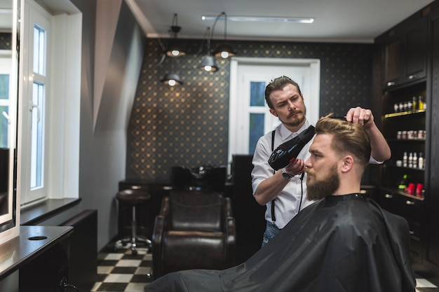 Barbiere con asciugatrice per asciugare i capelli dell'uomo