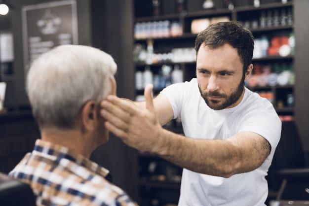 Barbiere e cliente in studio di parrucchiere