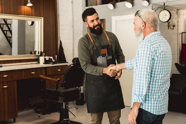 Barbiere e cliente maschio senior che agitano le mani