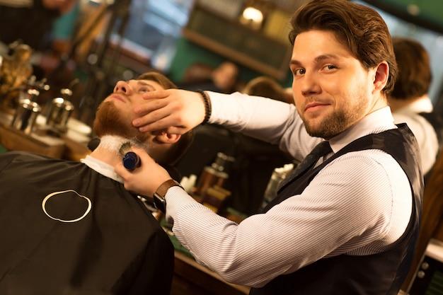 Barbiere professionista che lavora nel suo barbiere