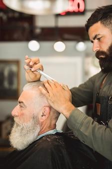 Barbiere professionista con le forbici che disegna i capelli dell'uomo anziano