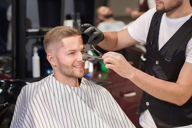 Barbiere rimozione maschera nera dal volto di uomo nel negozio di barbiere