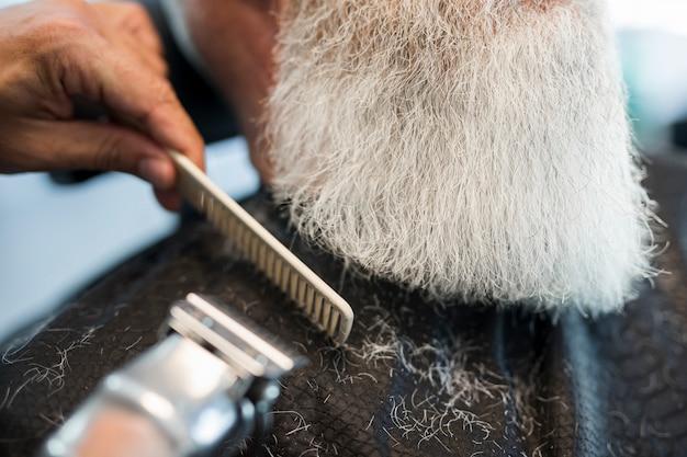 Barbiere taglio barba al cliente in salone