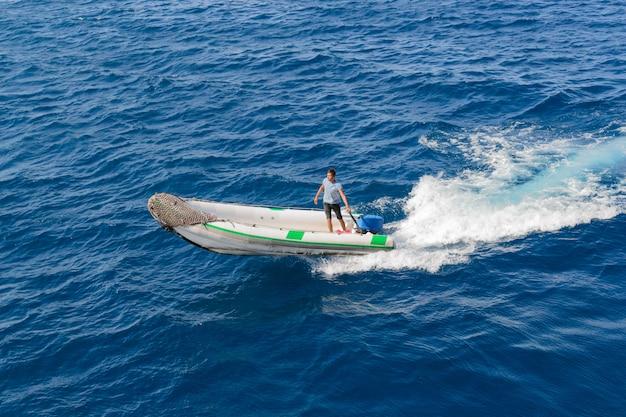 Barca a motore con un uomo in mare