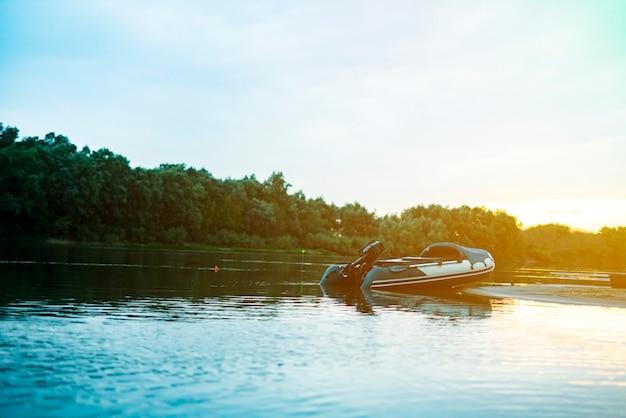 Barca a motore gonfiabile del pescatore sulla riva sabbiosa del fiume al crepuscolo.