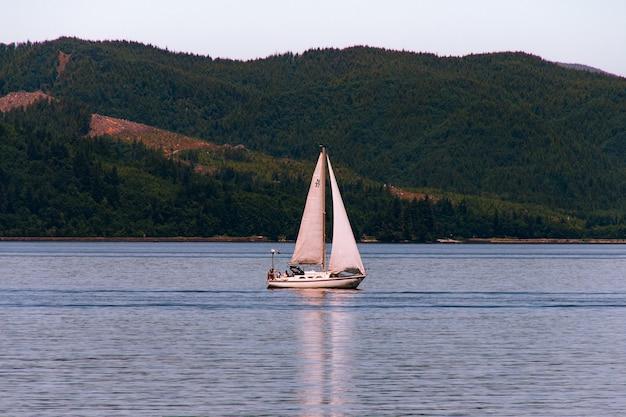 Barca a vela che naviga in un bellissimo fiume con una foresta su una ripida collina