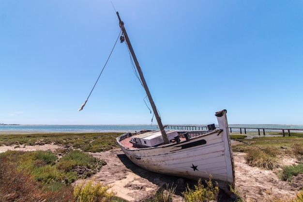 Barca abbandonata sulla vegetazione sulle dune di sabbia delle regioni paludose di ria formosa situate nell'algarve, portogallo.