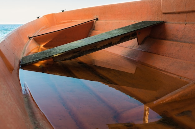 Barca arancione piena d'acqua