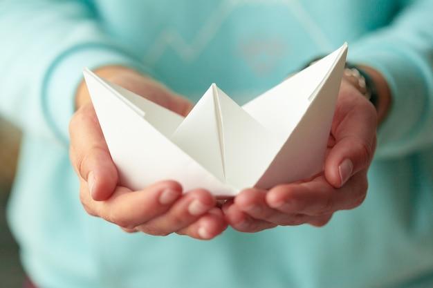 Barca bianca di origami nelle mani della donna