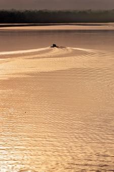 Barca che crea onde nelle acque dorate del fiume all'alba. itanhaem, stato di san paolo, brasile