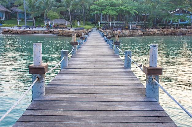 Barca del pilastro del ponte di legno nel mare e nel cielo luminoso.