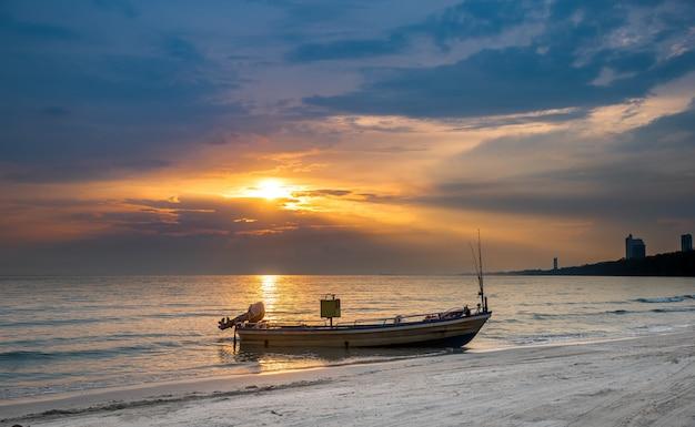 Barca dell'industria della pesca con l'illuminazione calda del cielo al tramonto