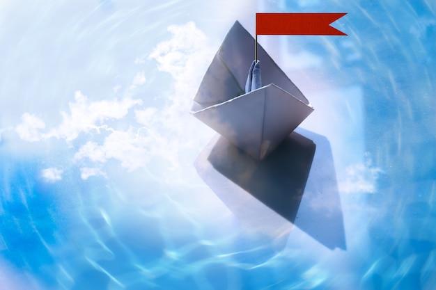 Barca di carta astratta vela sull'acqua con onde e increspature