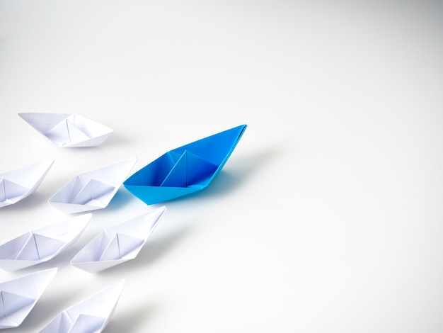 Barca di carta blu che conduce tra navi bianche