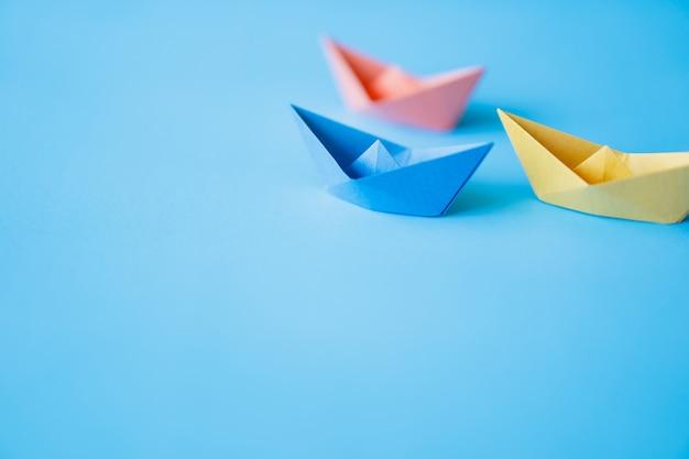 Barca di carta di colore pastello su fondo pulito con lo spazio della copia