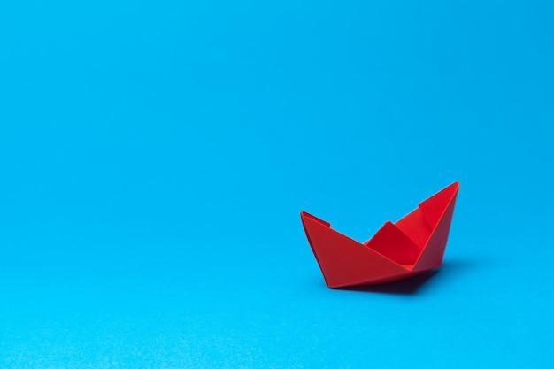 Barca di carta origami su sfondo blu