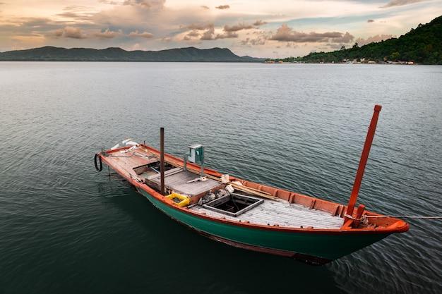 Barca di legno della pesca nello scape del lago shore.